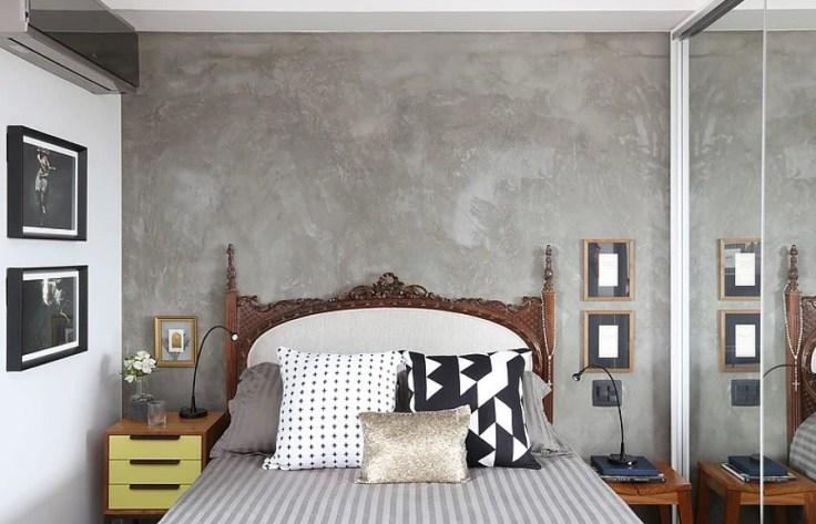 Parede de cimento queimado na cabeceira da cama no quarto.