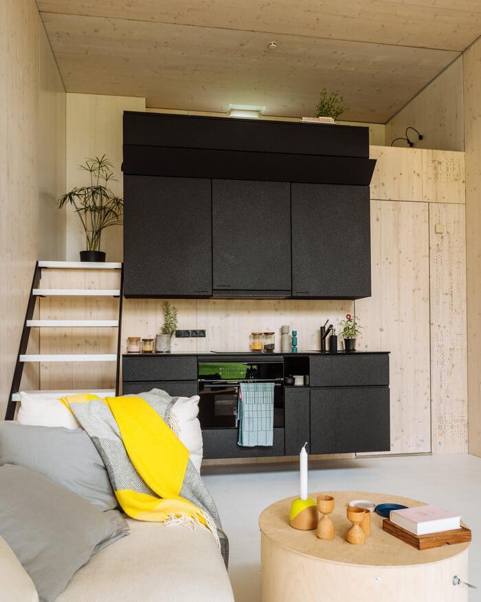 Vista da sala em primeiro plano, com a cozinha ao fundo e a escada que leva ao mezanino.
