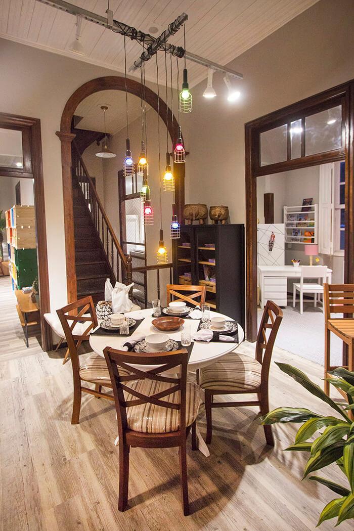 Mesa de jantar à frente e, ao fundo, quarto, sala e escada que leva ao sótão