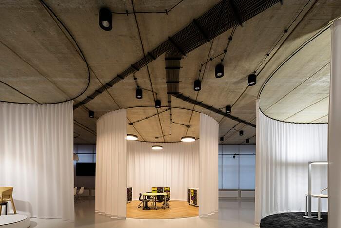 móveis são expostos em espaços circulares envoltos por cortinas.