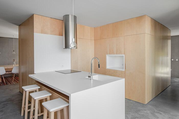 O centro do térreo é ocupado por um bloco revestido de madeira, onde fica a cozinha