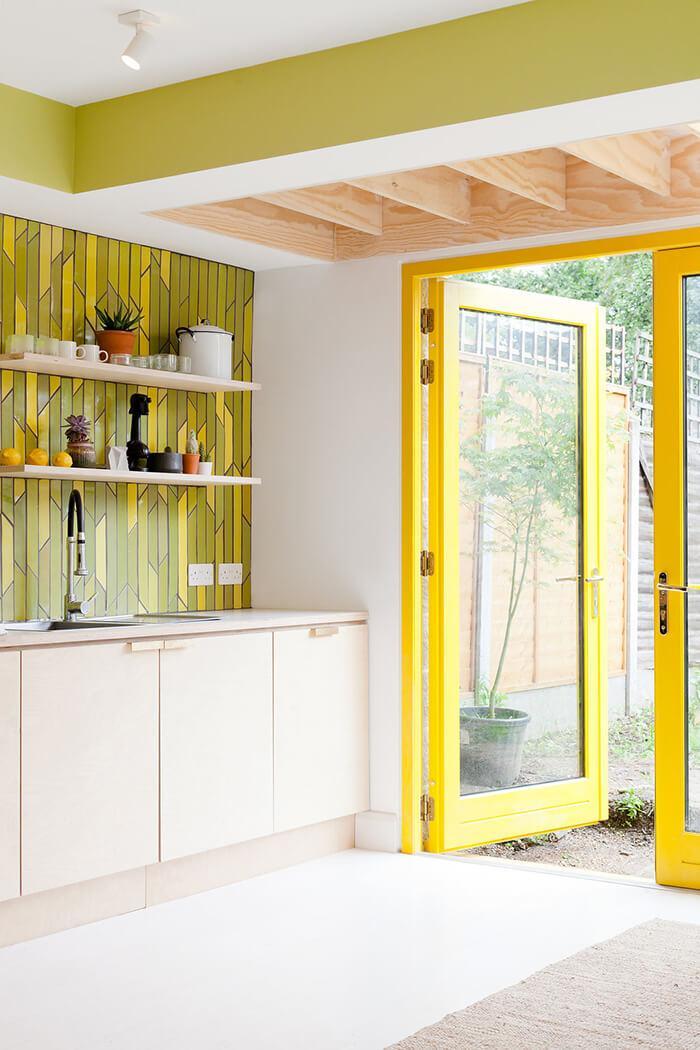 Ao lado da cozinha da casa londrina fica a porta de vidro com caixilhos amarelos que leva ao quintal