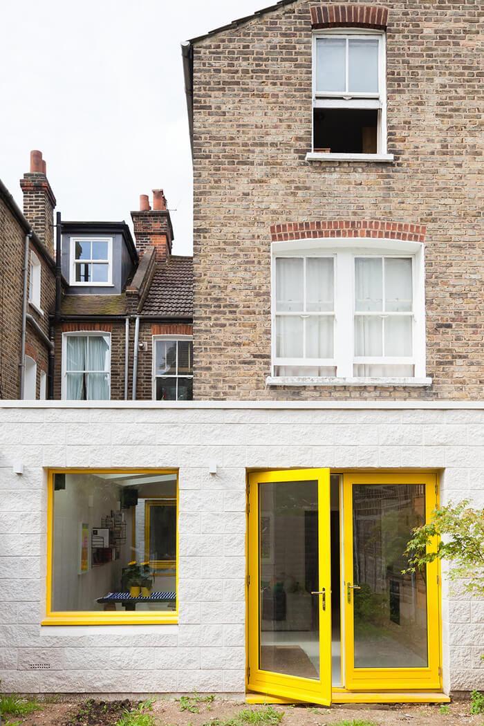 Fachada dos fundos de casa vitoriana de tijolo ampliada com blocos de cimento branco.