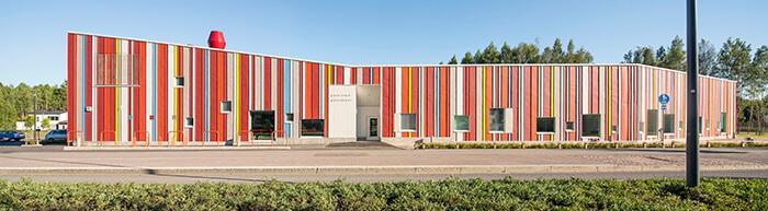 Fachada frontal bem extensa de creche finlandesa revestida de chapas metálicas coloridas