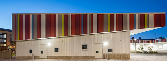 A fachada de trás é de madeira pintada de branco, com beiral de chapas metálicas coloridas