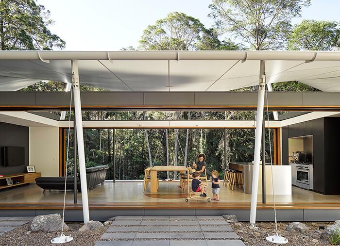 Mãe e dois filhos brincam na área ocupada por sala e cozinha abertas da Tent House. Atrás, paredão da floresta