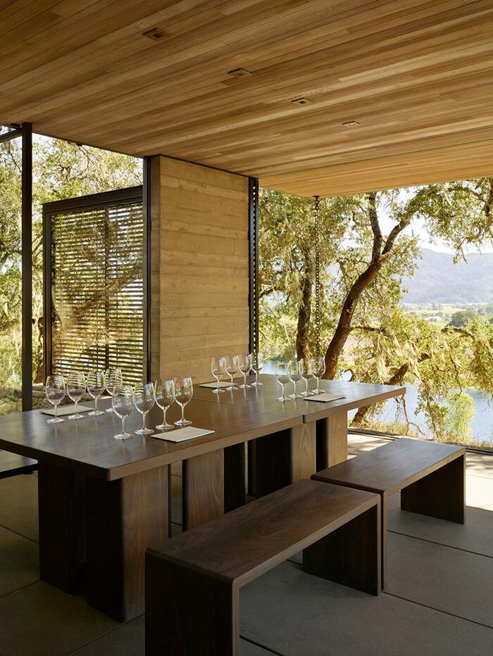Mesas e bancos prontos para receber degustadores de vinho na Quintessa