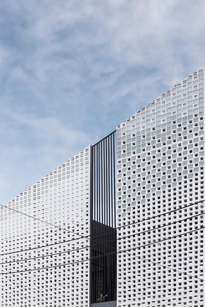 Detalhe dos blocos vazados de concreto na fachada de prédio projetado por Ekar Architects