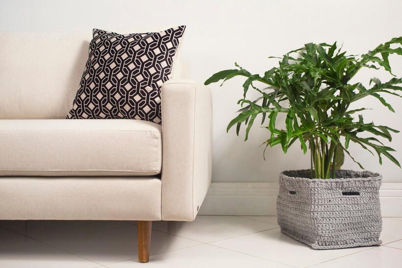 Sala de estar com planta natural dentro de cachepo de croche