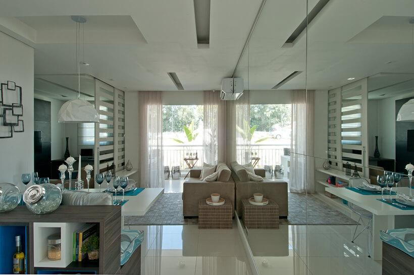 sala de estar com espelho atrás do sofá dando a sensação de sala duplicada