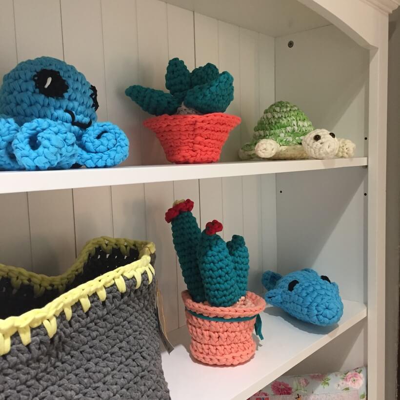 Brinquedos e plantas de croche decorando uma estante