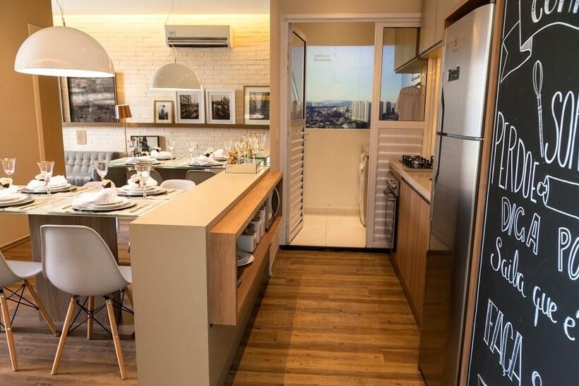 sala e cozinha conjugadas com o mesmo acabamento que nao se confundem com a lavanderia