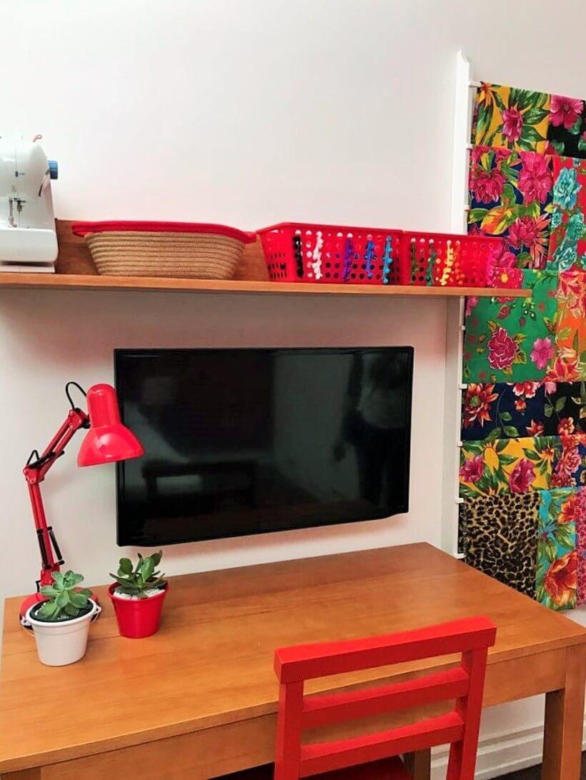 escrivaninha com TV colada a parede para evitar o acumulo de coisas no tampo