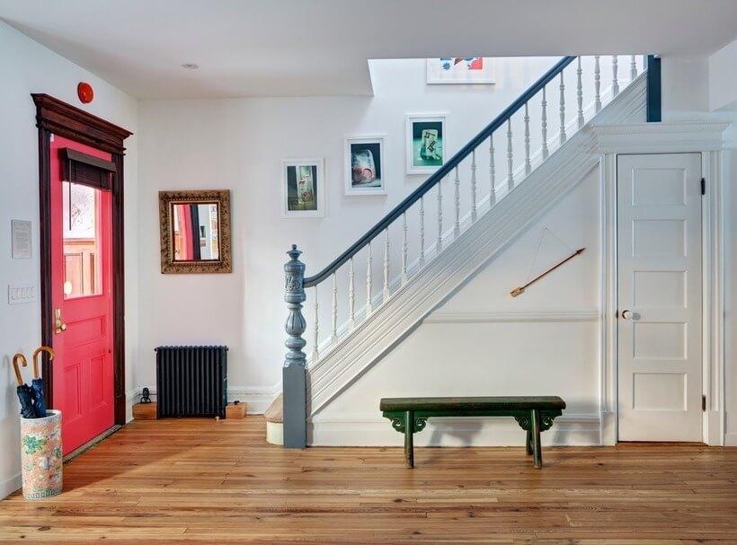 Originais da construção, a porta de entrada e o guarda-corpo da escada apontam para uma mesma ideia: pintura colorida para destacar os entalhes na madeira.