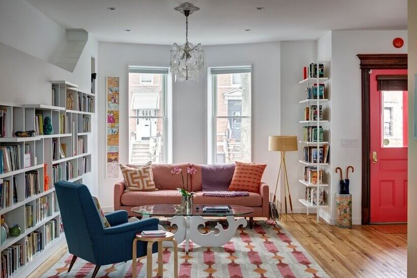 A cor está nos detalhes: na poltrona azul, no sofá cor-de-rosa, na manta e nas almofadas estampadas que repetem os tons do tapete.