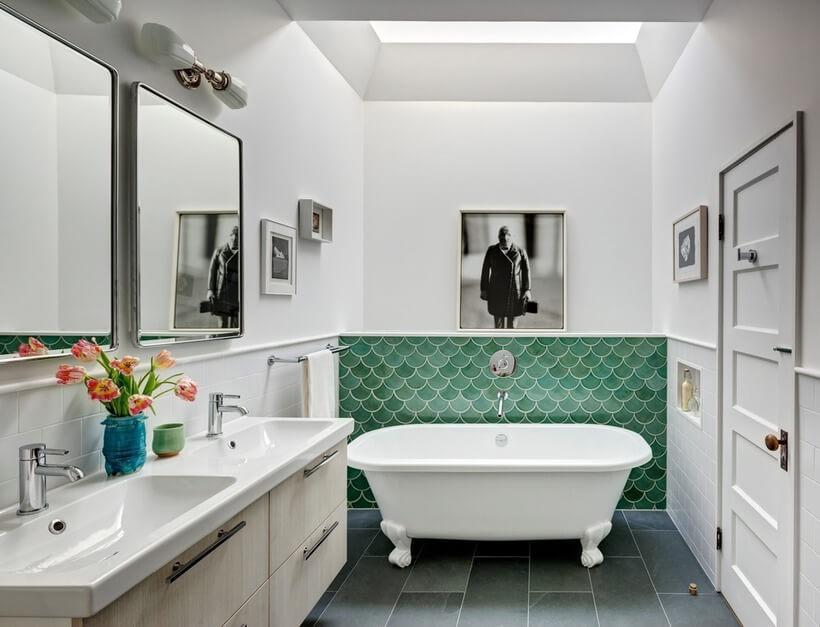 O charme de antigamente aparece em cada detalhe do banheiro: nas arandelas acima dos espelhos, na banheira de louça com pés, nas meias-paredes azulejadas que combinam peças brancas retangulares e verdes no formato escama de peixe.