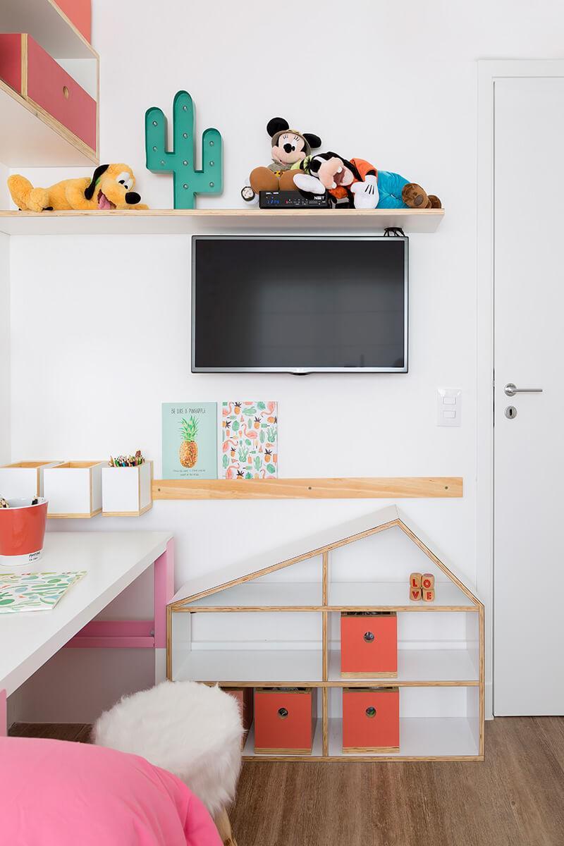espaço com prateleira baixa em formato de canaleta e tv no quarto de menina