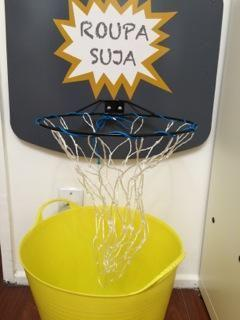 cesto de roupa suja para crianças brincando como se fosse cesta de basquete