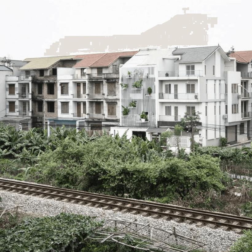 vista da parte de tráz com jardins pendurados na parede de casa no vietnã construida para ter luz natural e com muito verde