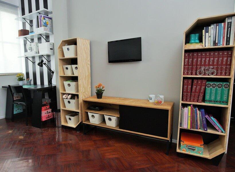 sala de tv com estantes altas para organizar livros e rack baixo no centro e tv acoplada na parede