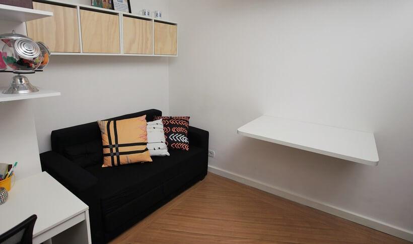 bancada em sala de estar fixada junto da parede que serve para servir como bancada de estudos