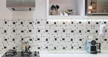 Detalhe da parede da pia de cozinha com revestimento em azulejo preto e branco geométrico