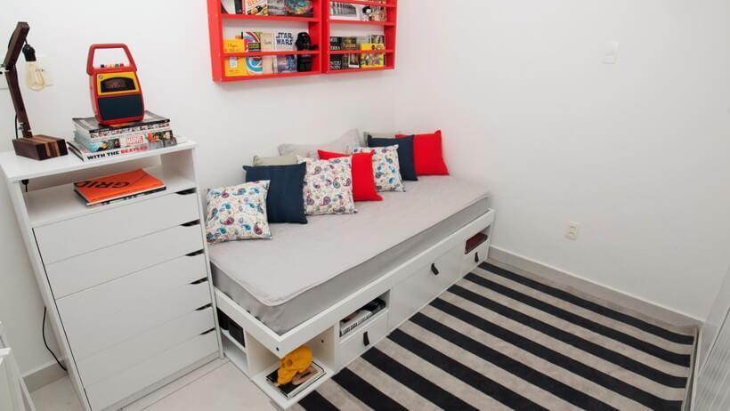 quarto de solteiro com cama com nichos e gavetas branca encostada junto a parede