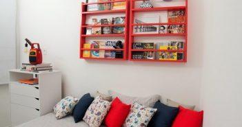 quarto de hóspedes com detalhe para a parede onde a cama está encostada, onde se encontram duas estantes de parede vermelhas penduradas para armazenar livros