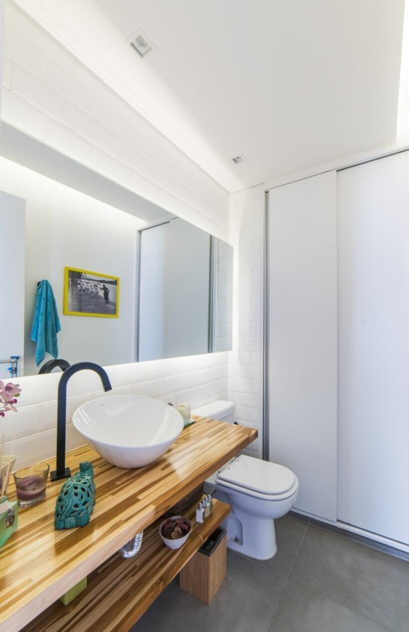 lavabo com espelho grande e bancada de madeira aparente no Apto Sumaré - Pietro Terlizzi (23)