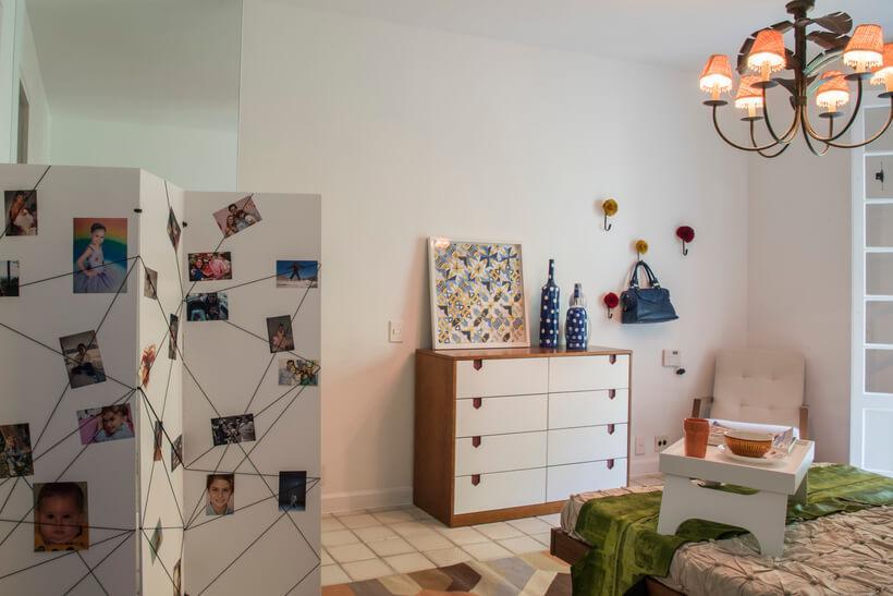 Biombo elástico no quarto de casal com fotos penduradas no biombo