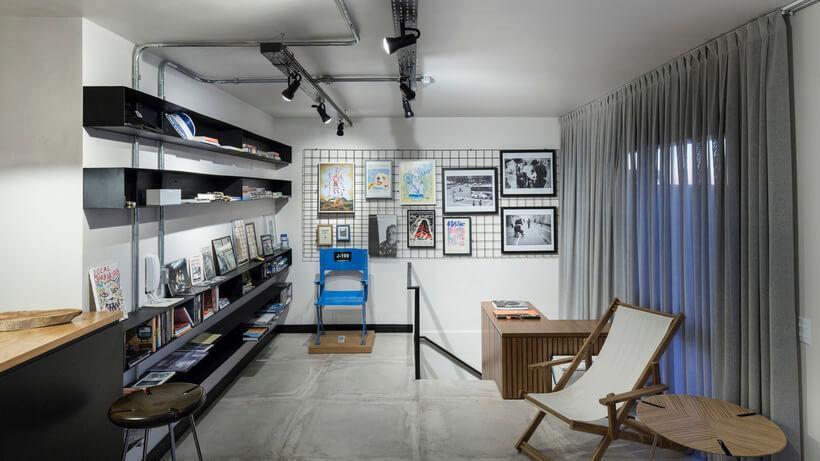 Escritório com painel de metal ao fundo para pendurar e grampear fotos