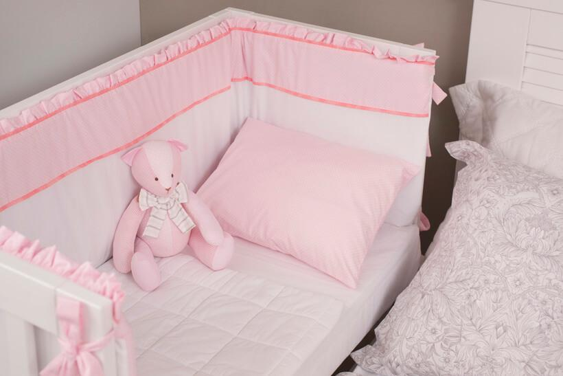 cama auxiliar com roupas de cama brancas e rosa recem limpadas