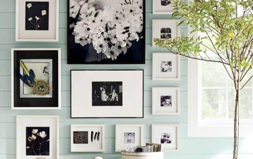Parede de casa com quadros de vários tamanhos e molduras pendurados