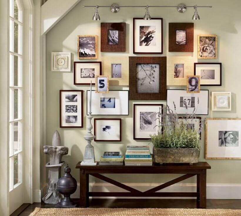 Parede do hall de entrada decorada com fotos de vários tamanhos e molduras diferentes