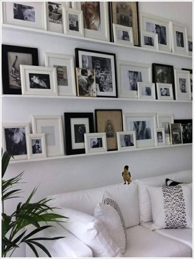 Quadros pendurados em prateleiras na parede atrás do sofá