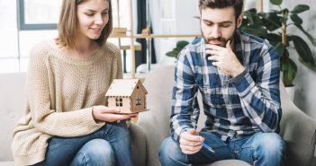 casal com miniatura de casa nas mãos pensando em alugar