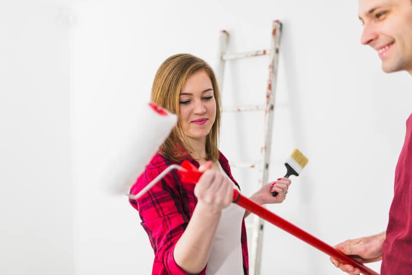 casal com pincel de tinta nas mãos preparando-se para pintar a parede