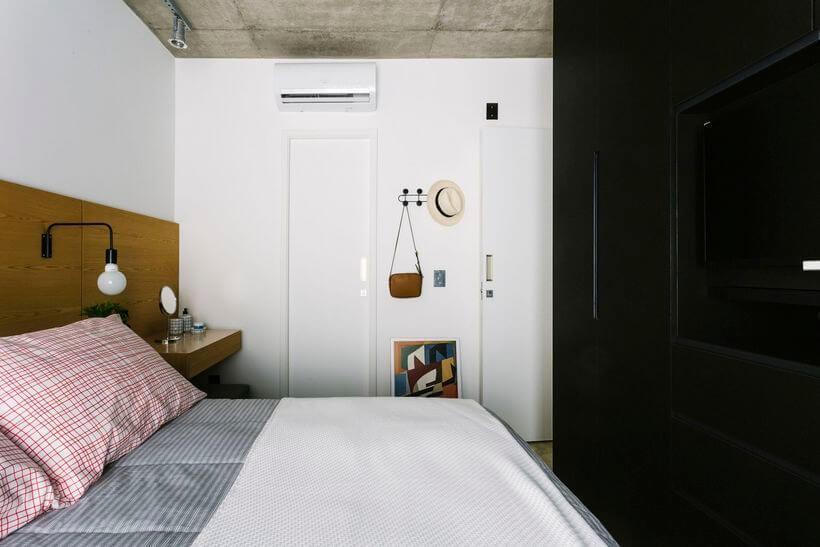 Quarto com uma bancada acoplada junto da cama servindo como criado-mudo