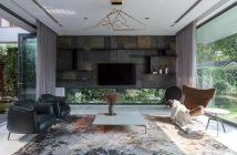 Sala de TV com painel de TV em ardósia e paredes de vidro pro ar circular