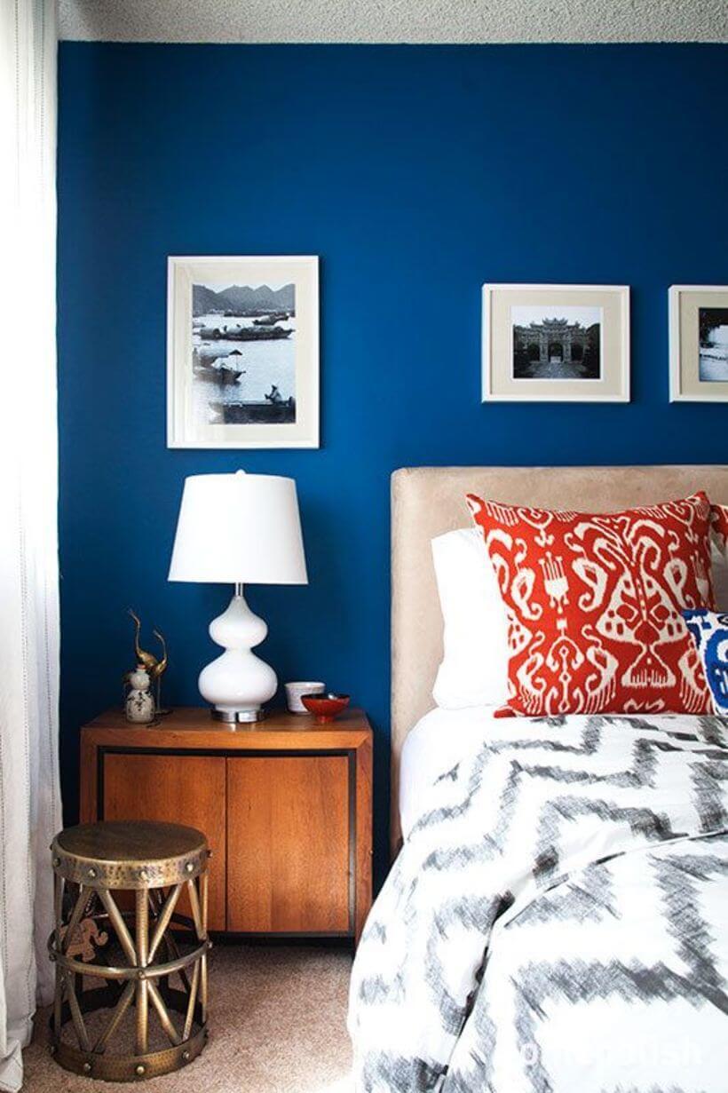 criado-mudo rústico em parede azul escura