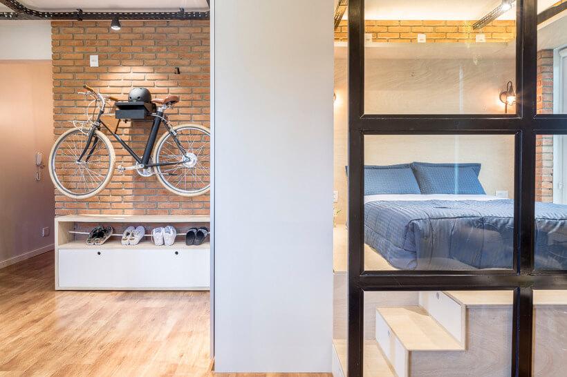 Decoracao sob medida - vista parcial do quarto de casal com parede de vidro e hall de entrada com bicicleta pendurada na parede de tijolo