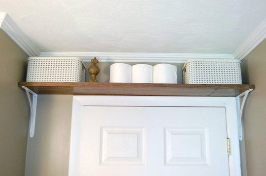 prateleira acima da porta do banheiro com toalhas.
