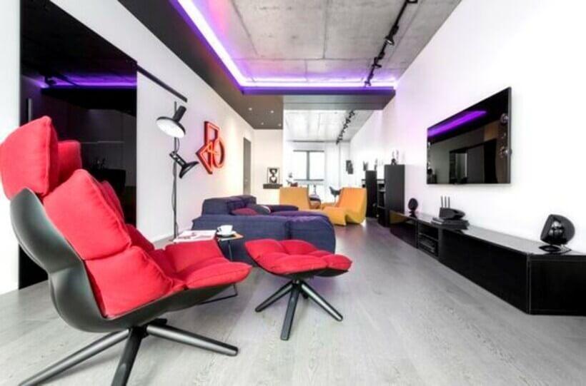 Decoração futurística em sala de tv, com poltrona de escritório estofada vermelha