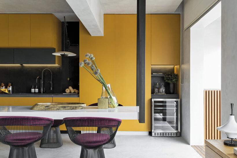 Cozinha integrada com armários amarelos e bancada suspensa