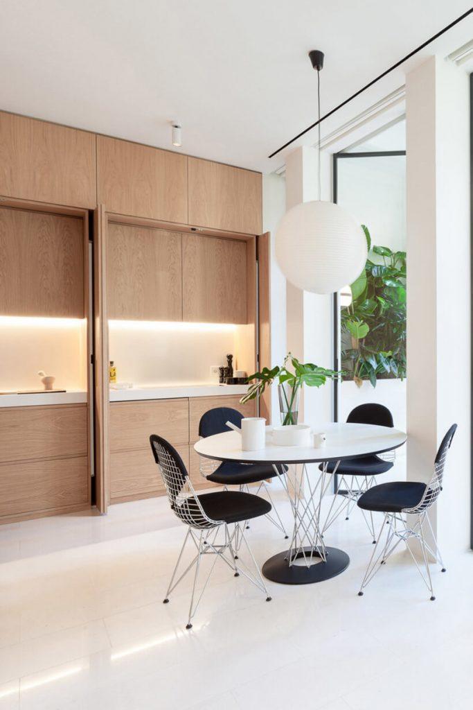 Sala de jantar com mesa redonda integrada com cozinha de embutir com armários escondidos