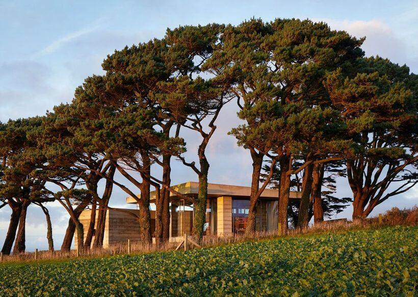 Secular Retreat vista de fora e ao longe, rodeada por árvores