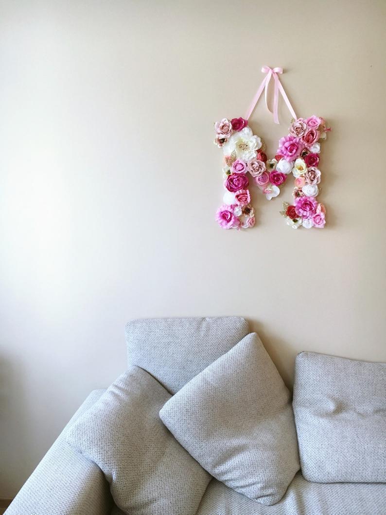 Letra decorativa feita com flores de papel crepom.